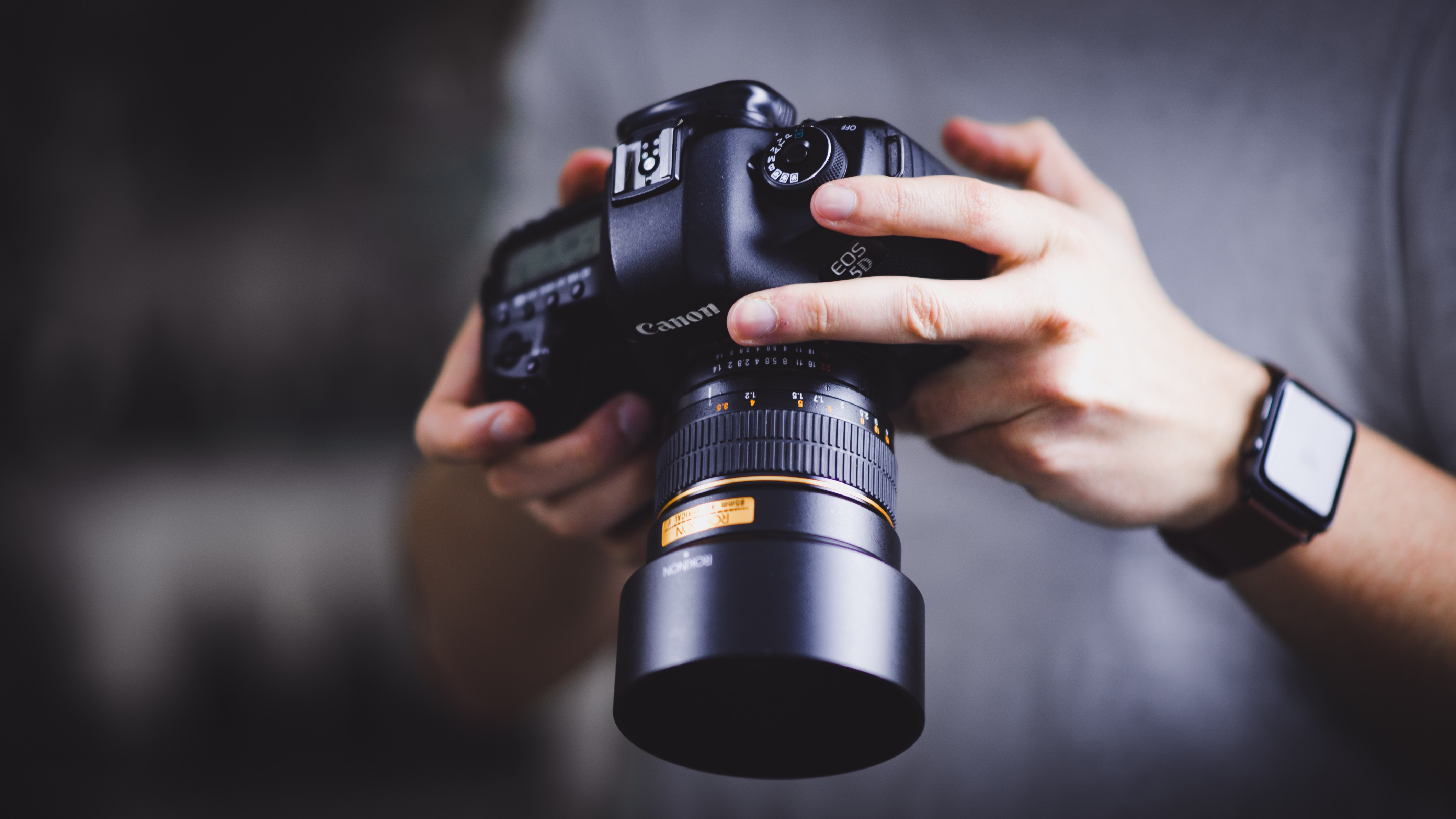 Person holding their Canon DSLR